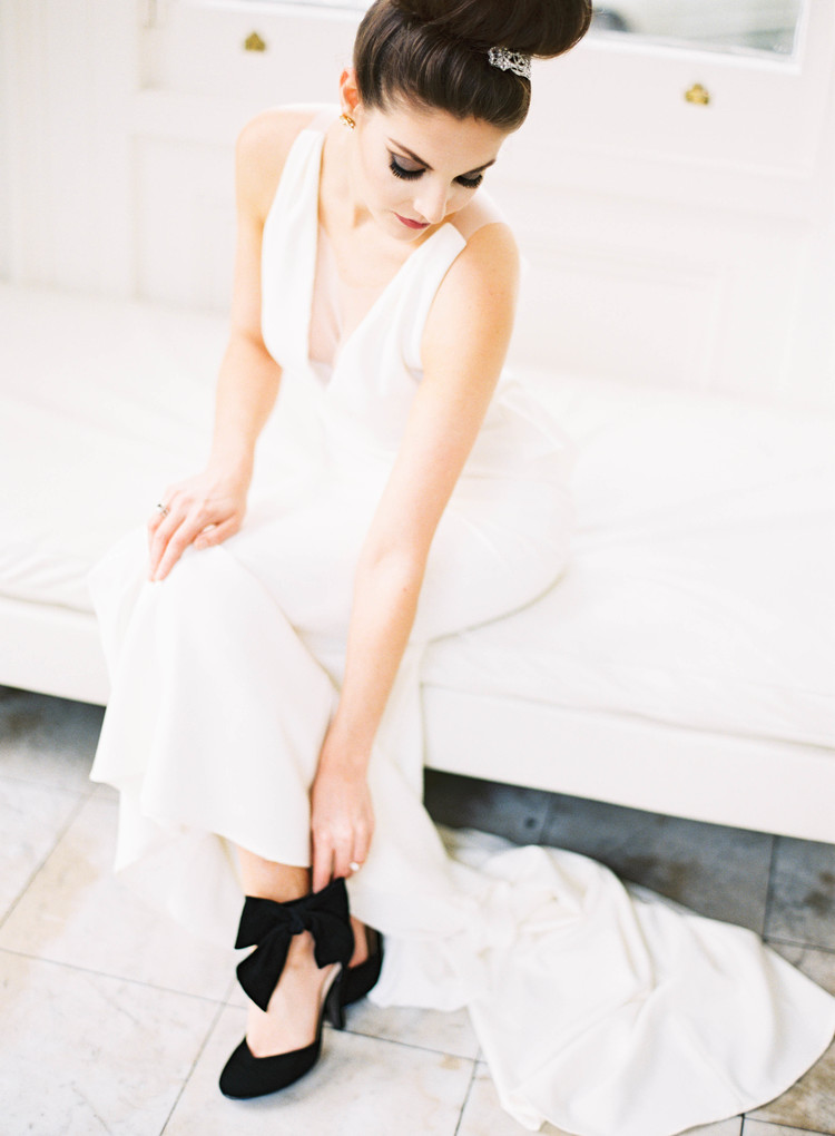 Bride in her wedding gown glancing down at her black wedding shoes under her dress