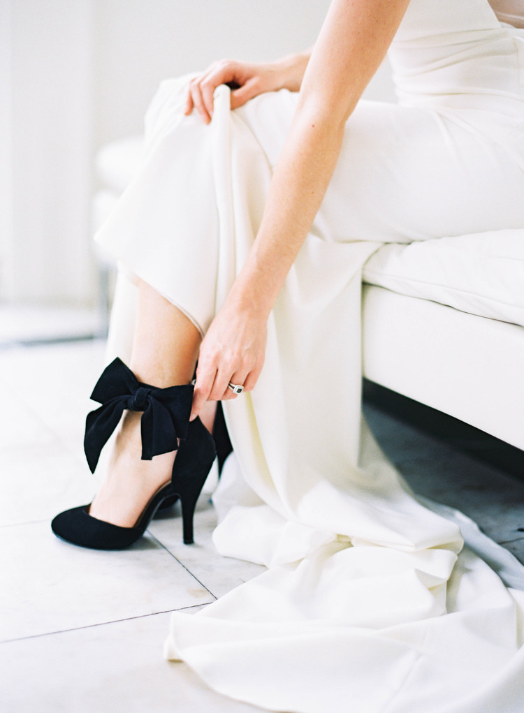 Bride zipping up her black velvet wedding shoes