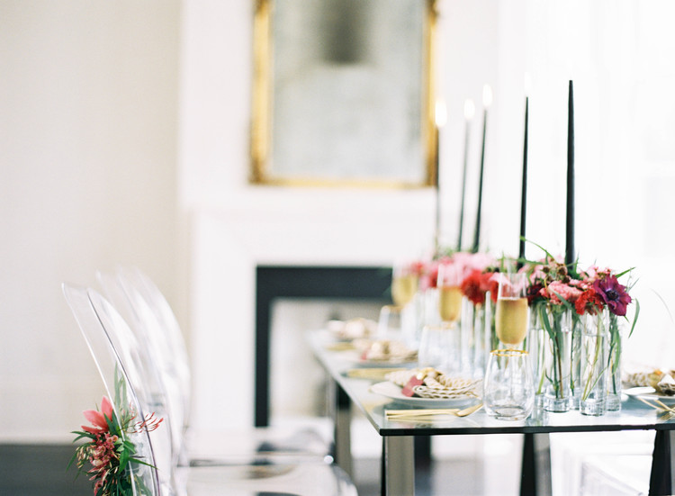 Detail shot of a seating arrangement with ghost chairs and pink florals down the center with tall black candle sticks