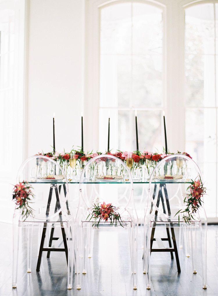 Ghost chairs in front of a table with tall black candlesticks in the middle of a table length floral arrangement