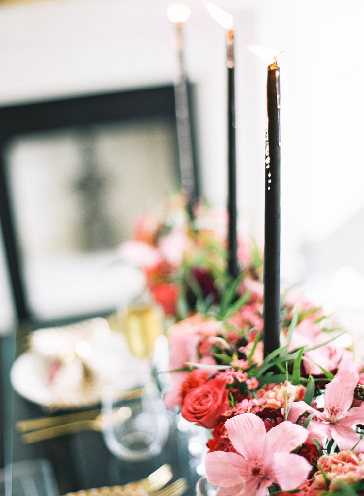 Black candlesticks lit in the middle of a pink floral arrangement on a table