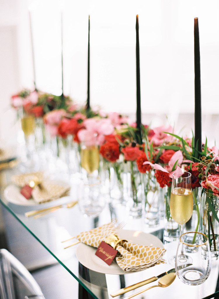 Red escort cards with gold calligraphy, gold flatware, champagne, black candle sticks and red and pink florals
