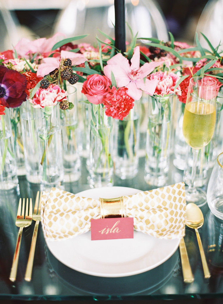 White napkins with gold detailing in a gold napkin ring next to a red escort card with gold names