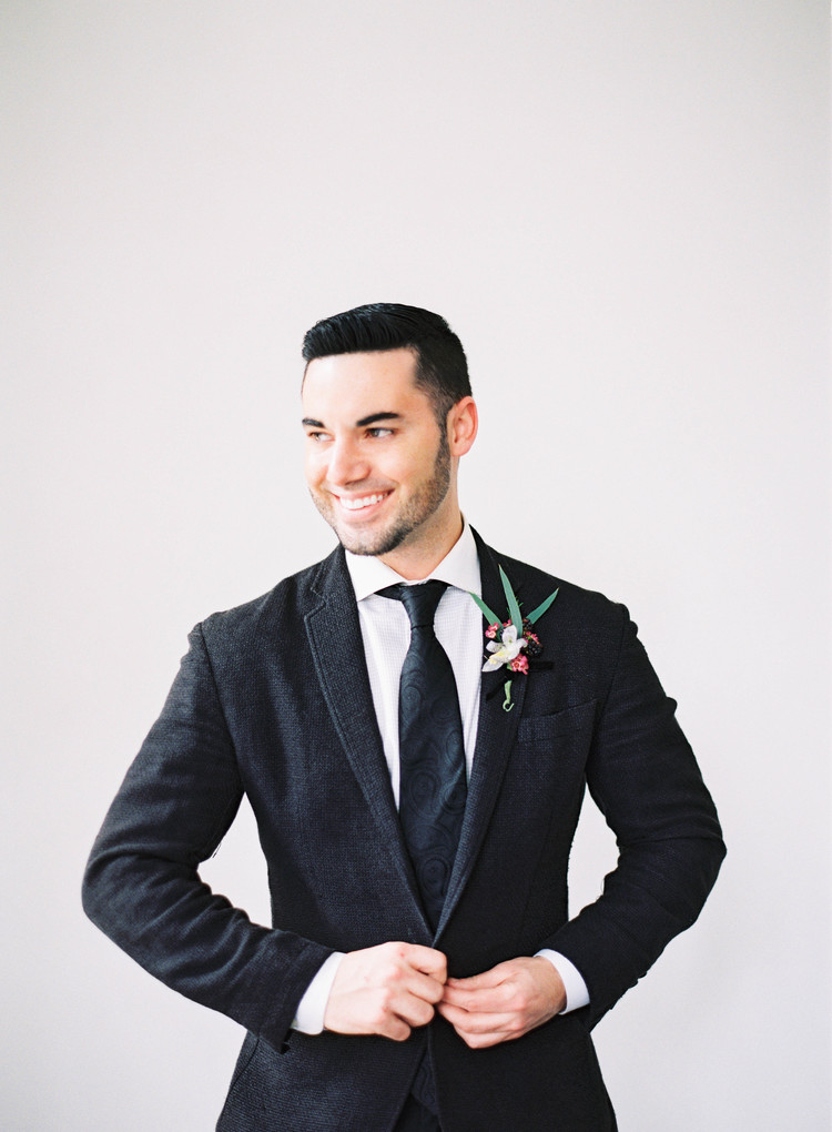 Groom smiling in a black suit with a white, pink and green boutonniere