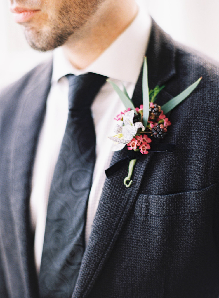 Groom s black suit, paisley black tie, and white, pink and green boutonniere