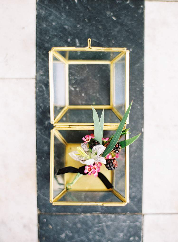 Boutonniere inside a gold glass shadow box