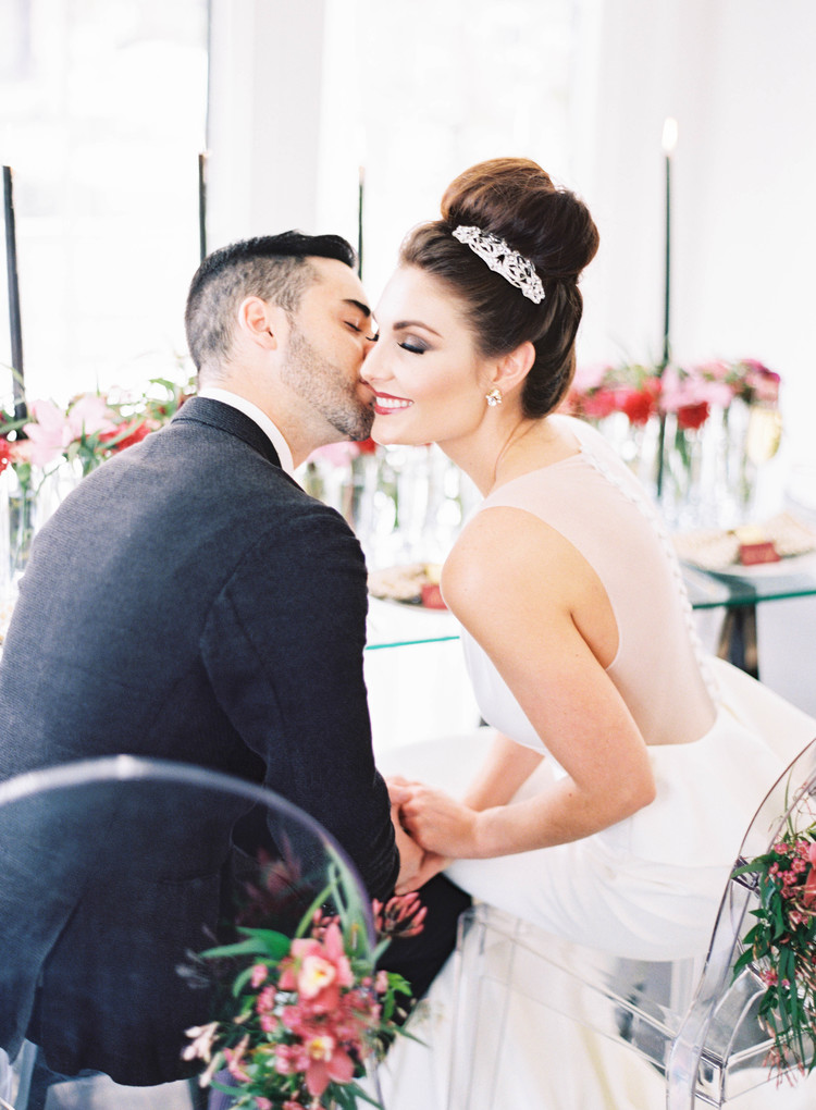 Groom kissing bride on the cheek sitting down in front of their table with pink and red florals down the center