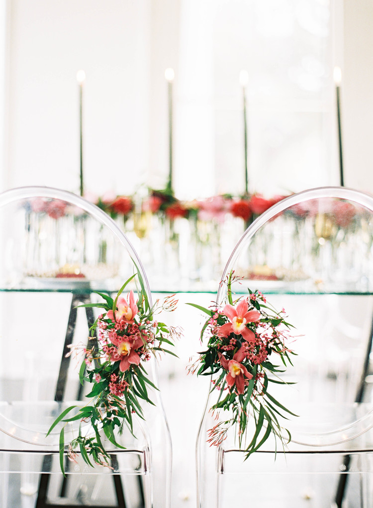 Ghost chairs with pink flowers and greenery attached to a side at the tables