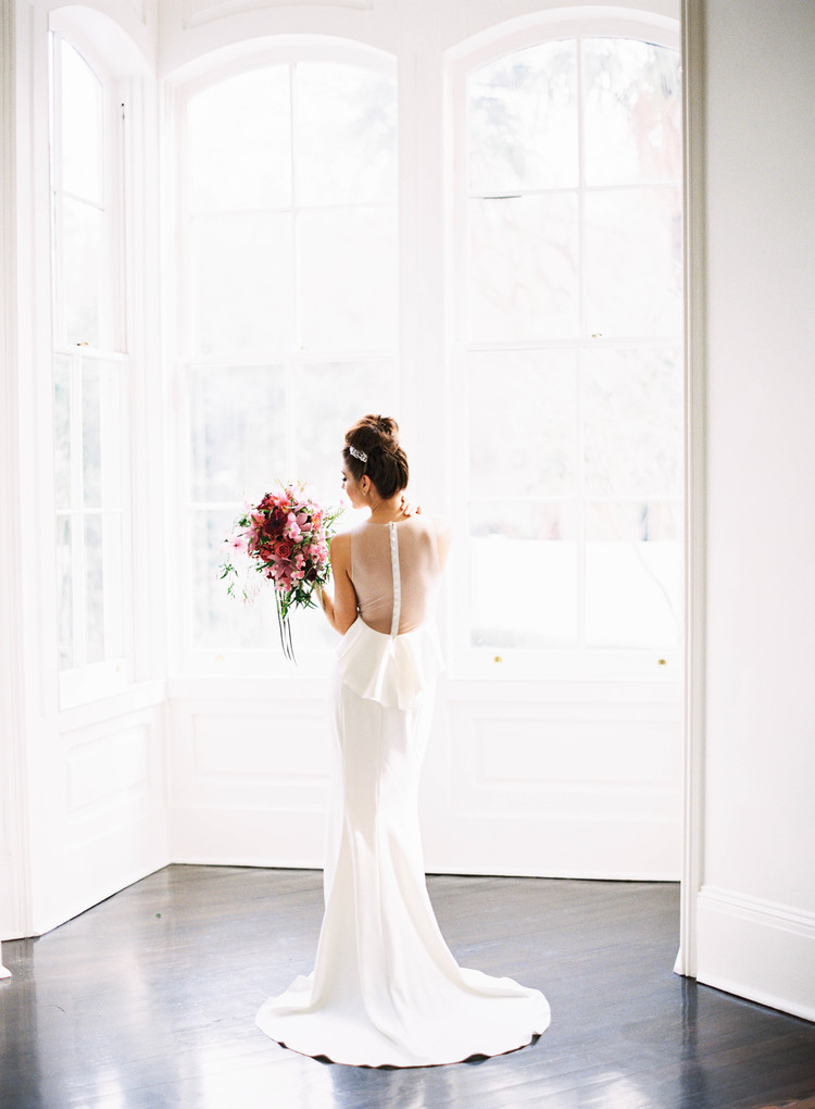 Bride standing in front of white windows in a long white wedding gown holding her lush bouquet