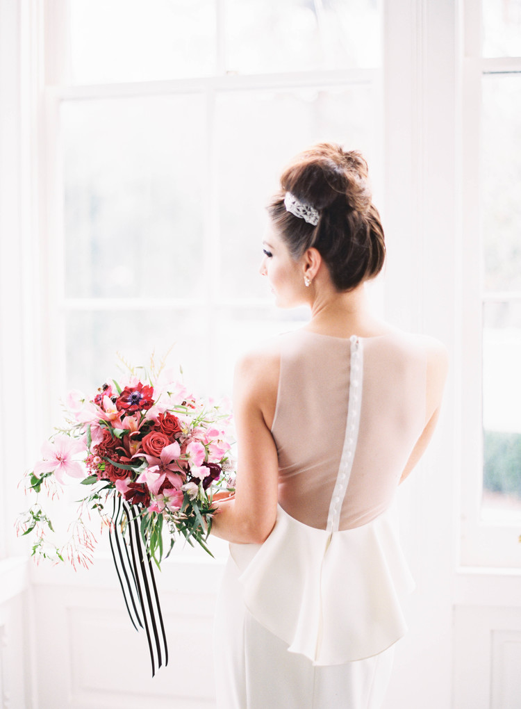 Bride in her wedding gown with see through mesh on the back and buttons down, holding her bouquet with black and white stripped ribbon tied around it