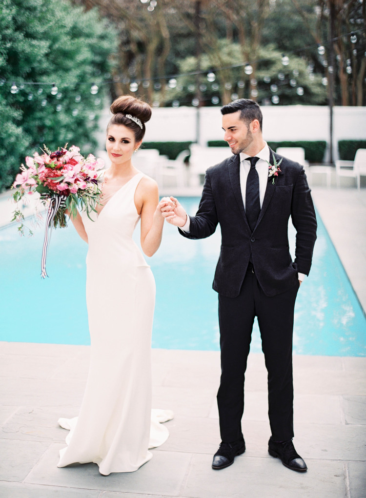 Bride and groom holding hands in front of a pool with her bouquet and string lights hanging in the background