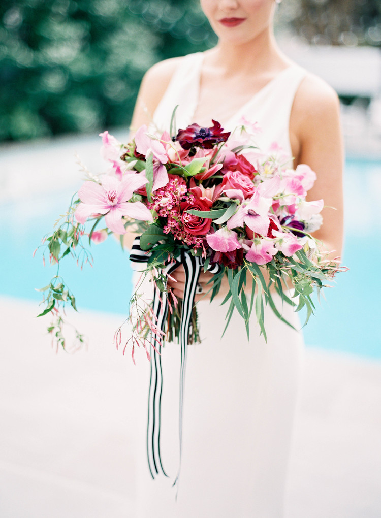 Lush bouquet with pink lilies, red roses, red carnations and greenery with a black and white stripped ribbon hanging