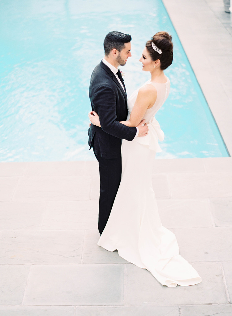 Couple hugging in front of a pool in their wedding attire