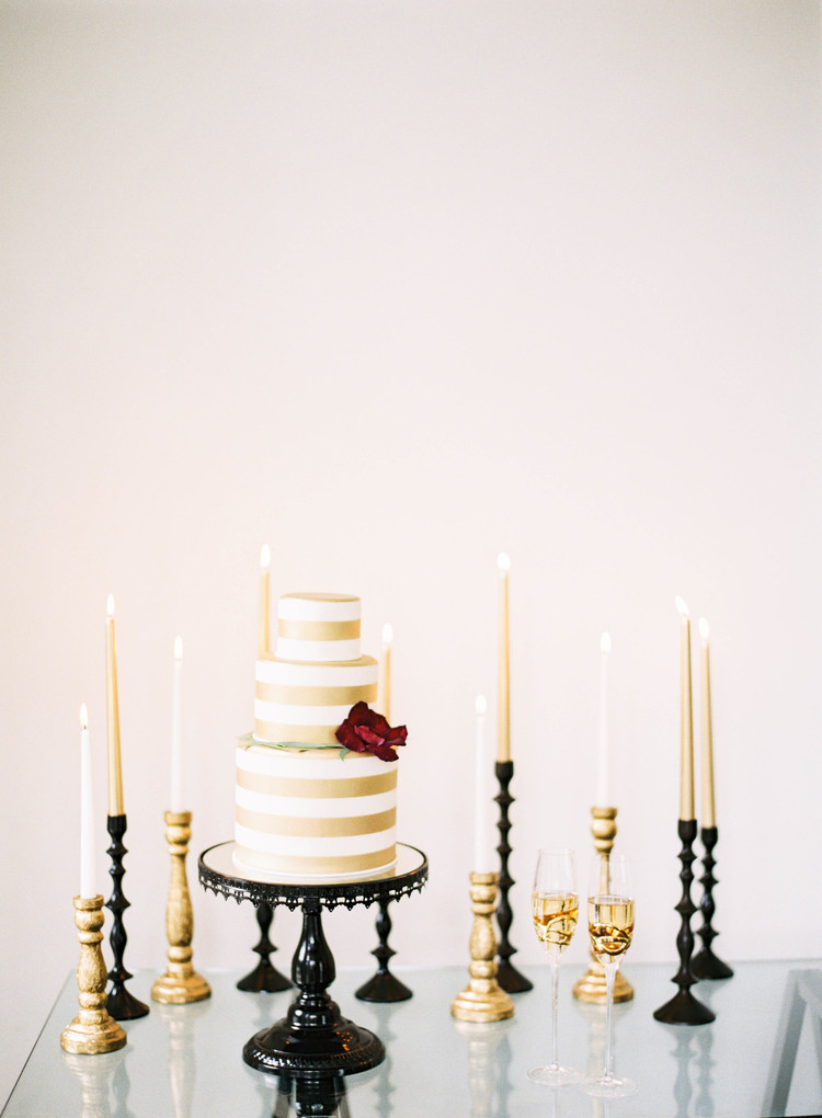 3 tiered white and gold striped cake with a red rose on the side and gold and white candles in black candlesticks