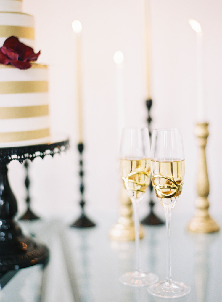 two glasses of champagne in front of black and gold candlesticks with gold and white candles