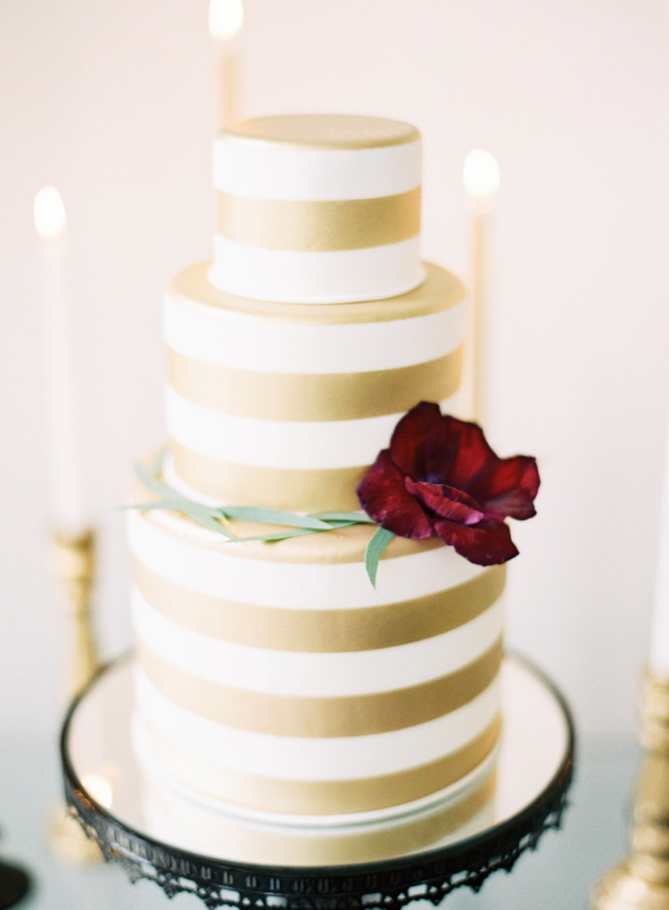 3 tier white and gold striped wedding cake with a dark red flower and greenery
