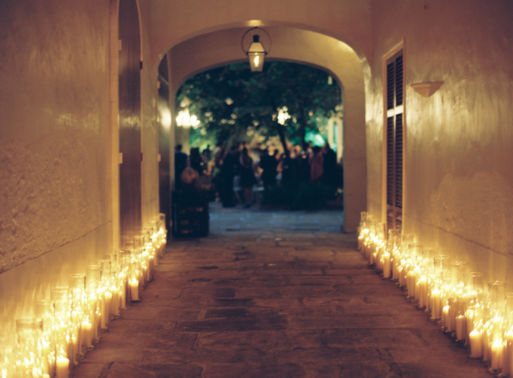arches entry way lined with many candles in clear candle vases