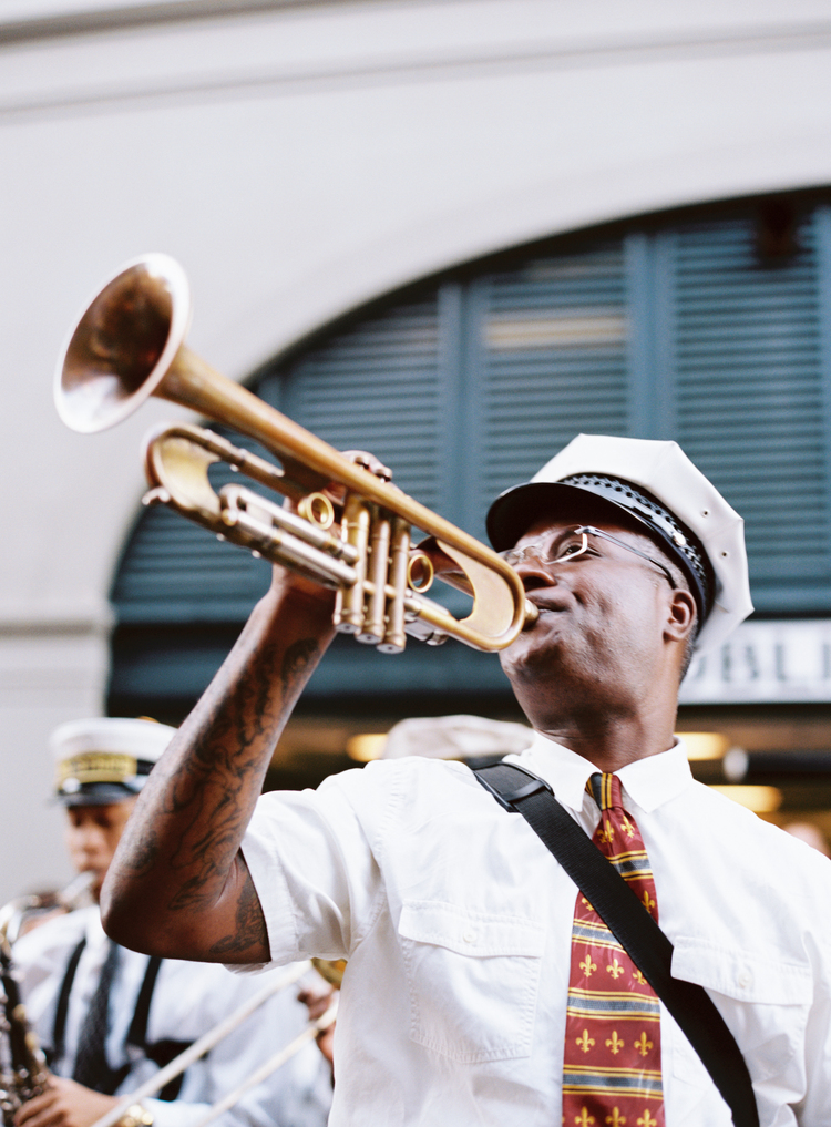 Trumpet player in a jazz band with a red fleur de lis tie