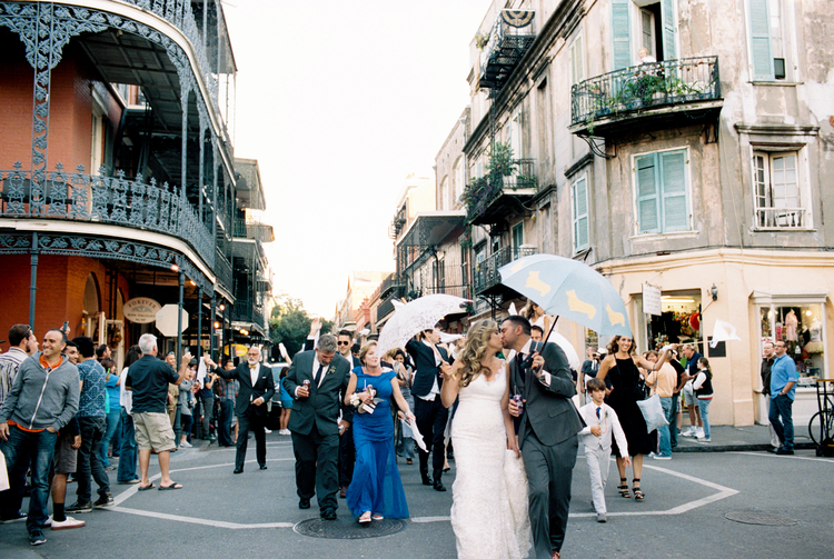 Bride and groom kiss white holding umbrellas second lining with their guests down the streets of the French Quarter in New Orleans