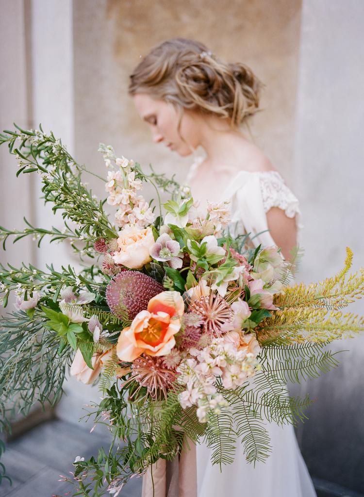 Bride looking over her shoulder holding her exotic wedding bouquet