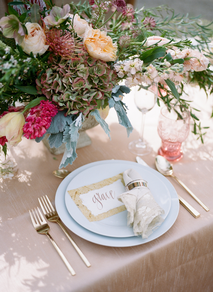 seating assignment written on white paper on top of white plates with gold silverware and pink water glasses