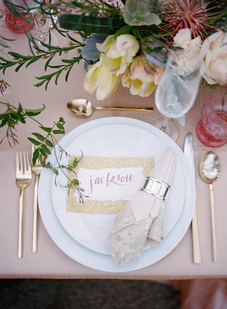 Tableware on a blush pink table linen with gold flatware