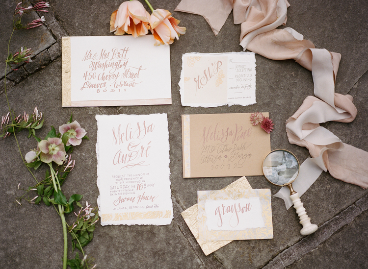 full view of the wedding invitation suite with blush colors, a flower and a magnifying glass