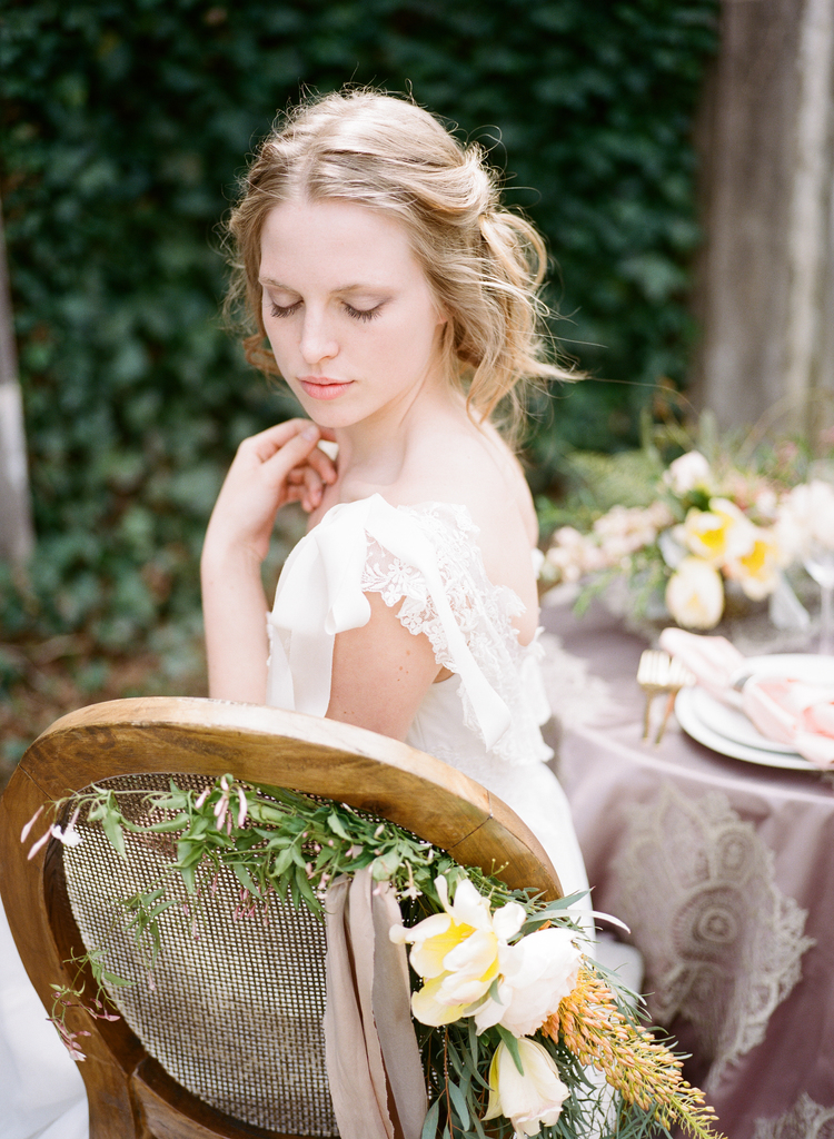 Bride sitting in a chair with greenery and yellow flowers tied the the back next to a blush table linen