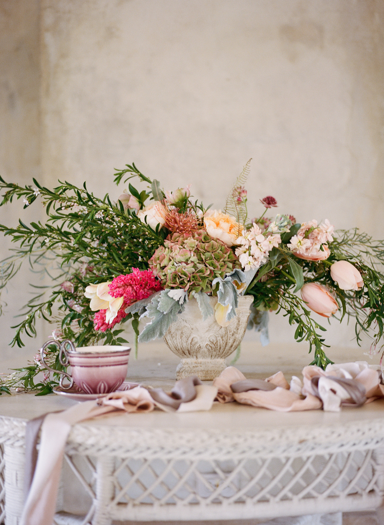 Beautiful cascading organic floral arrangement sitting on a white tabletop with blush ribbons