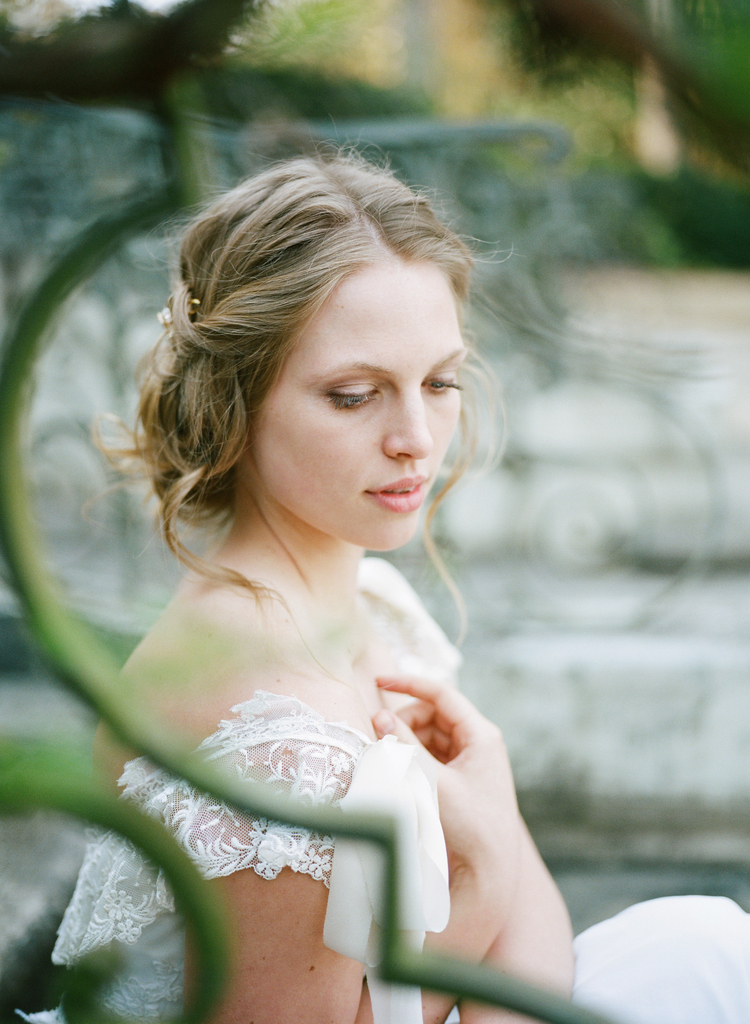 Bride with her hair twisted back in a low bun and delicate lace dress caps