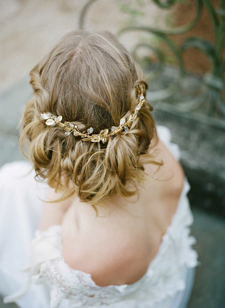 Back view of brides hair up do with a delicate gold hair piece