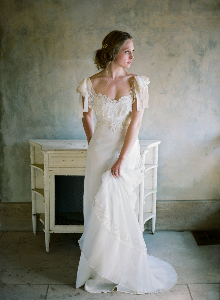 gorgeous full body picture of a bride in her lace vintage wedding gown leaning on a white table