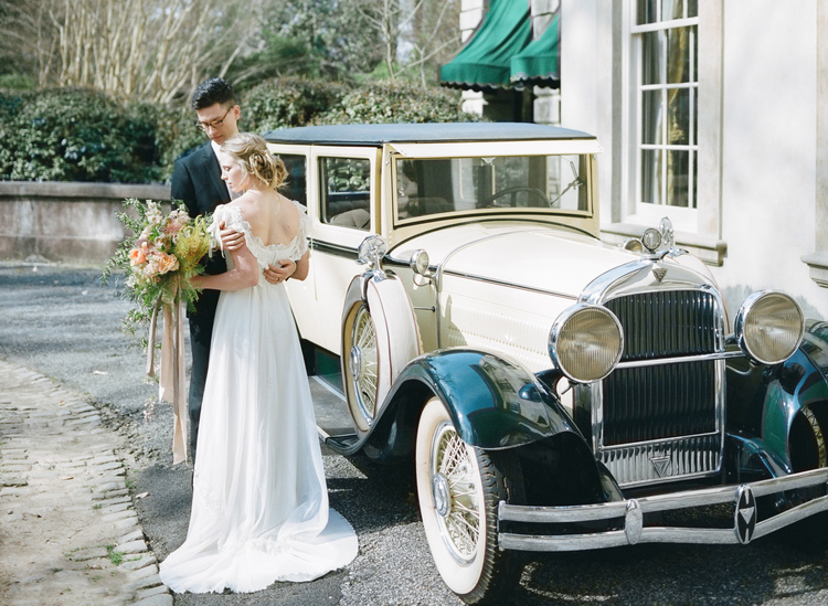 Bride and groom stand in front of a black and white 1930s car