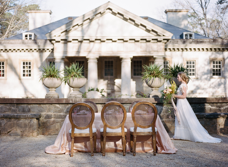 Bride walking in the back of a house with columns in front of a table with mahogany chairs and a blush table linen