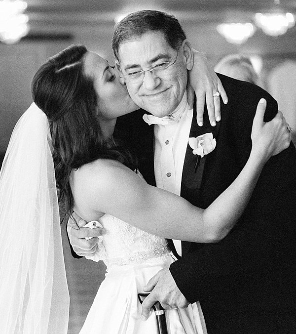 bride in long veil kissing her father on his cheek with him smiling and hugging her