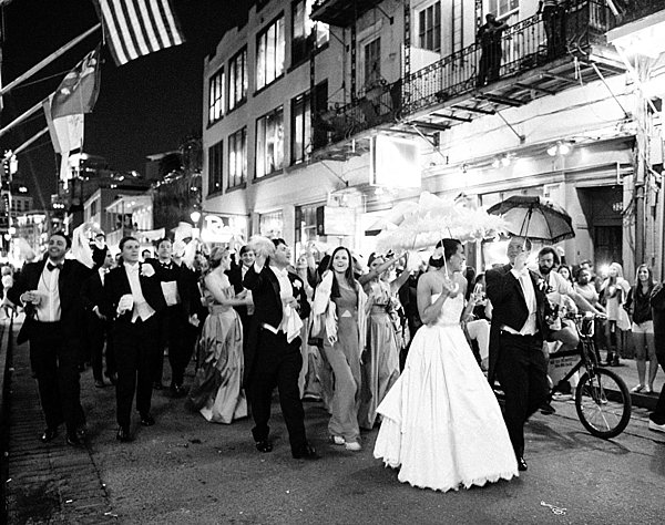 bride and groom holding parasols at night walking the the street leading a parade in the french quarter
