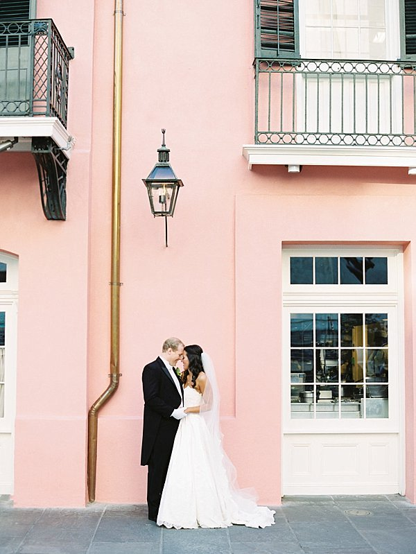 bride and groom holding hands outside pink building with gas lantern in new orleans