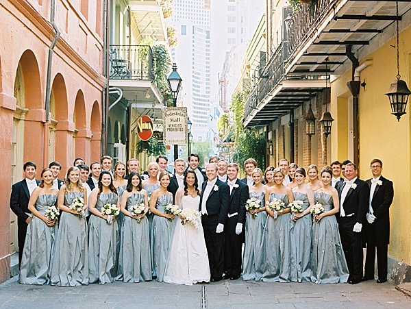 large wedding party in long gowns and tuxedos standing in between buildings in the french quarter