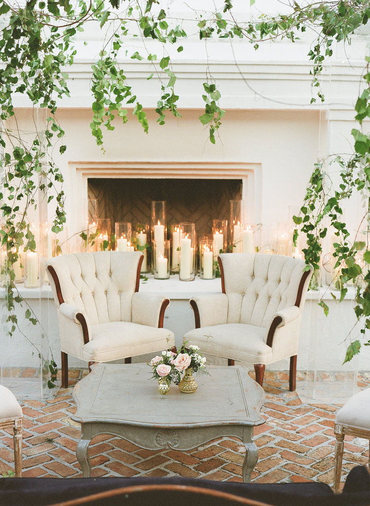 two cahris and a coffee table in front of an outdoor fireplace with candles and green vines