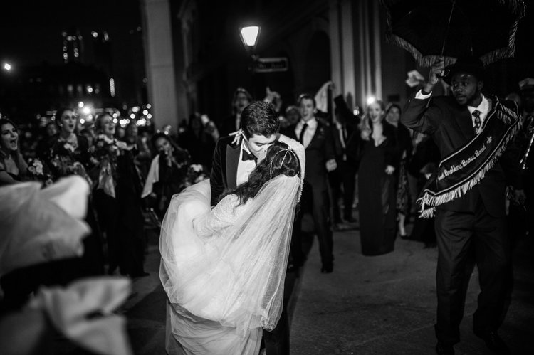 groom dips bride while kissing her and dancing in the street with people watching and cheering