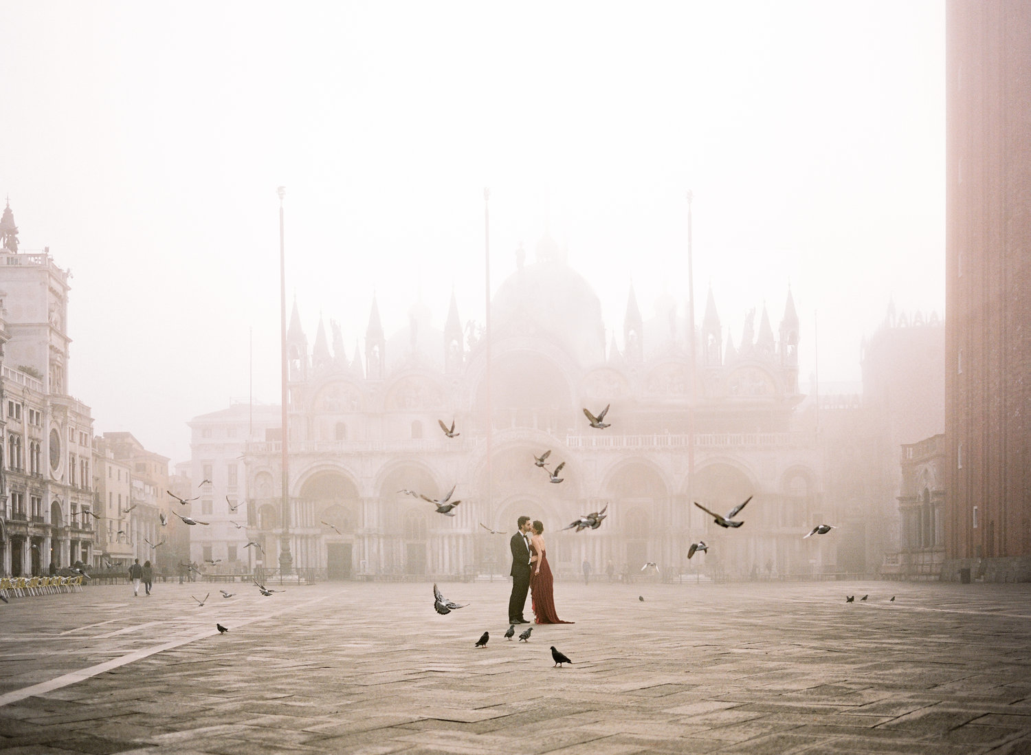 birds flying in a circle around a bride in a red dress kissing her group in an elopement in Venice Italy