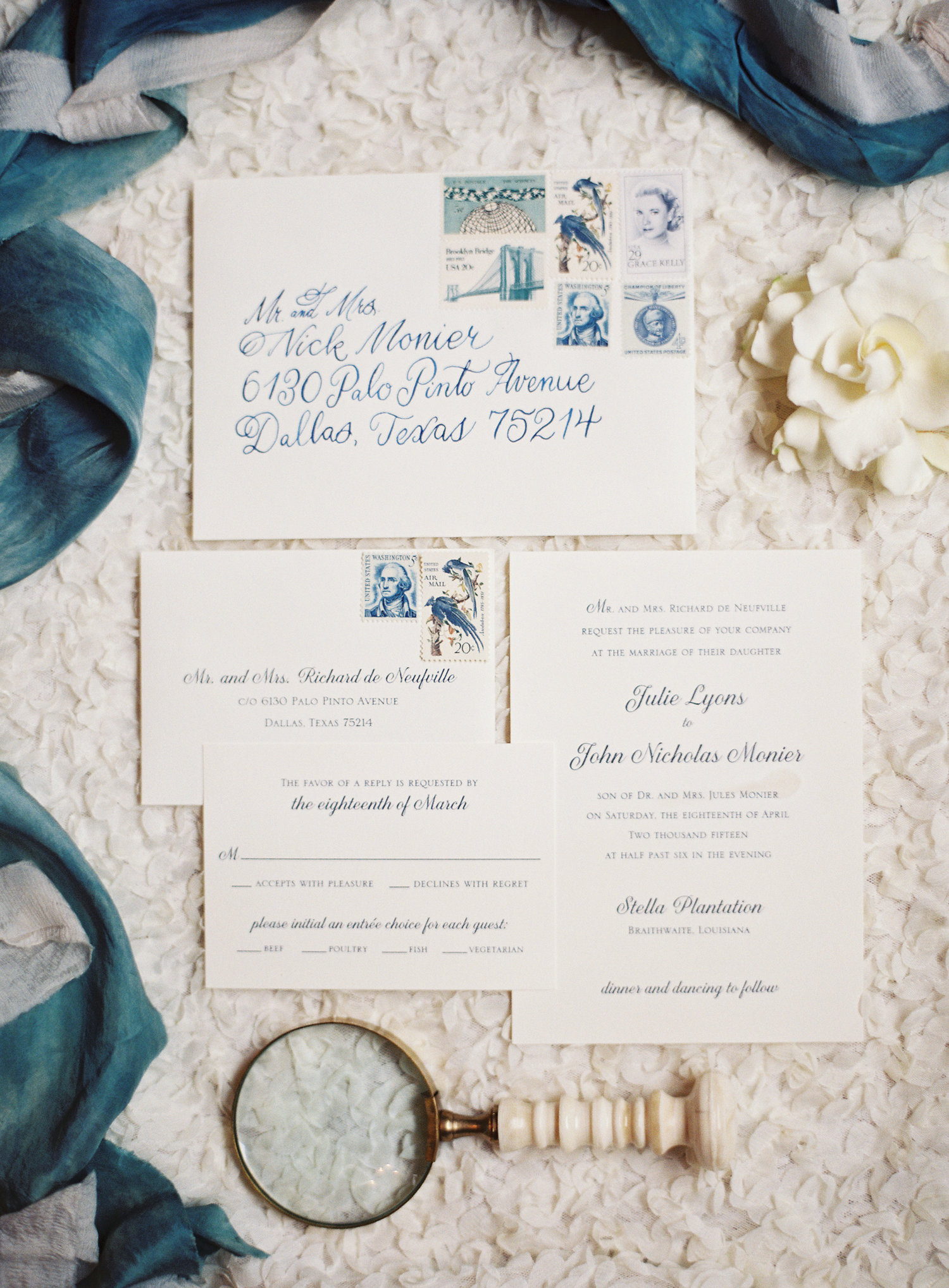 Ivory wedding invitation suite with blue calligraphy and a blue stamp story