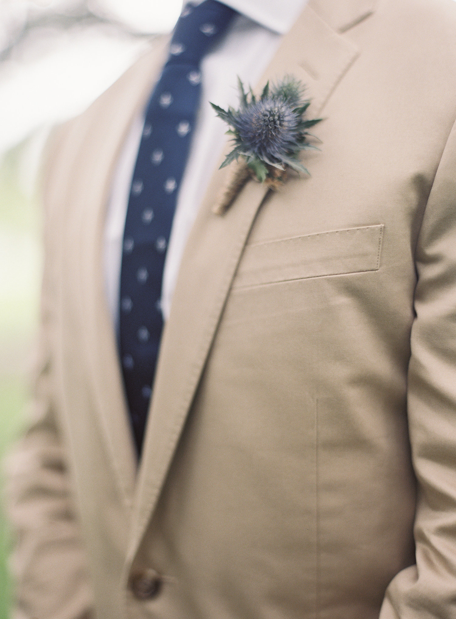 Grooms khaki suite with a blue pattern tie and a blue boutonniere