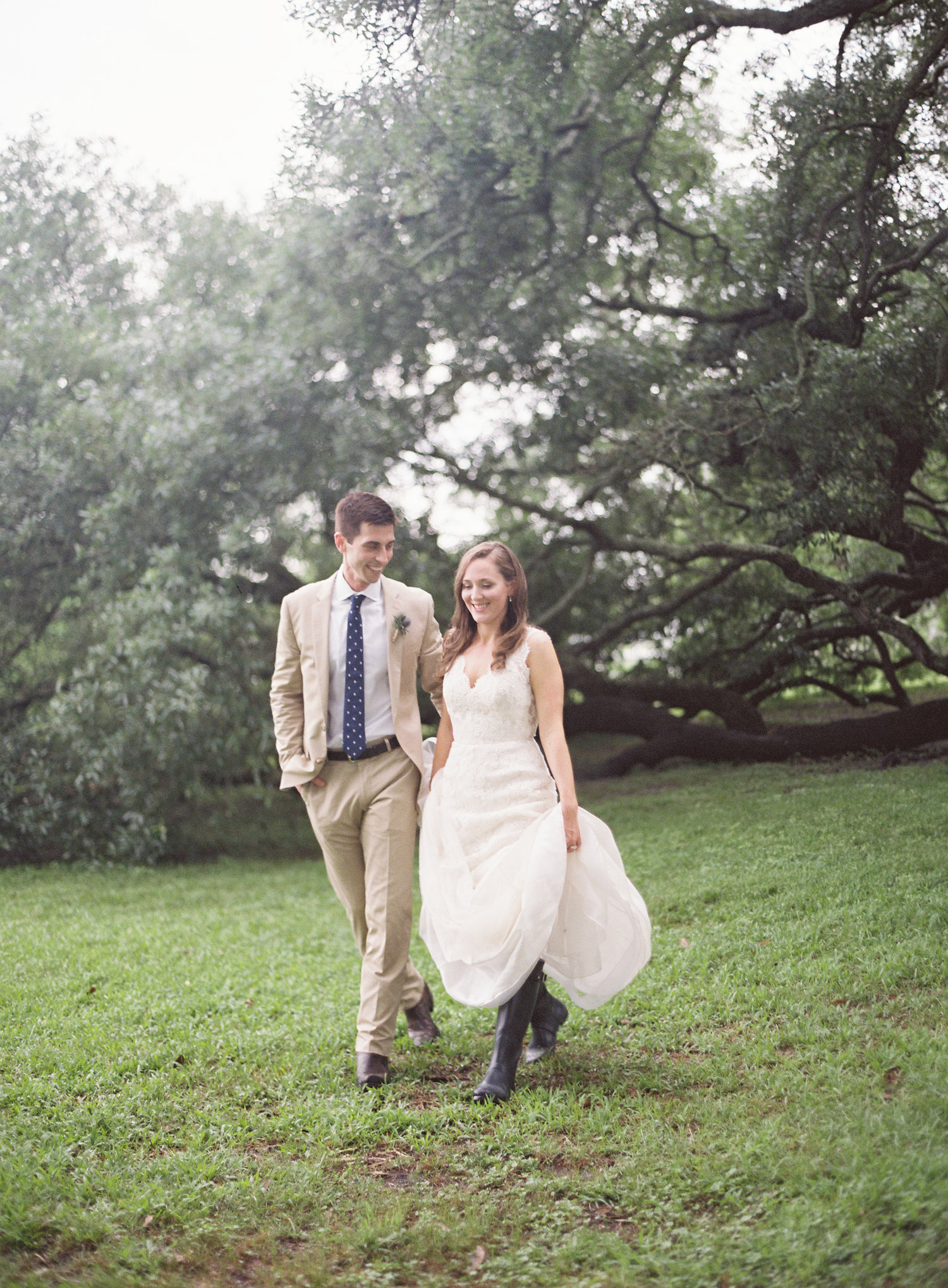 Bride and groom in their wedding dress and suite walking through the park with oak trees in the background
