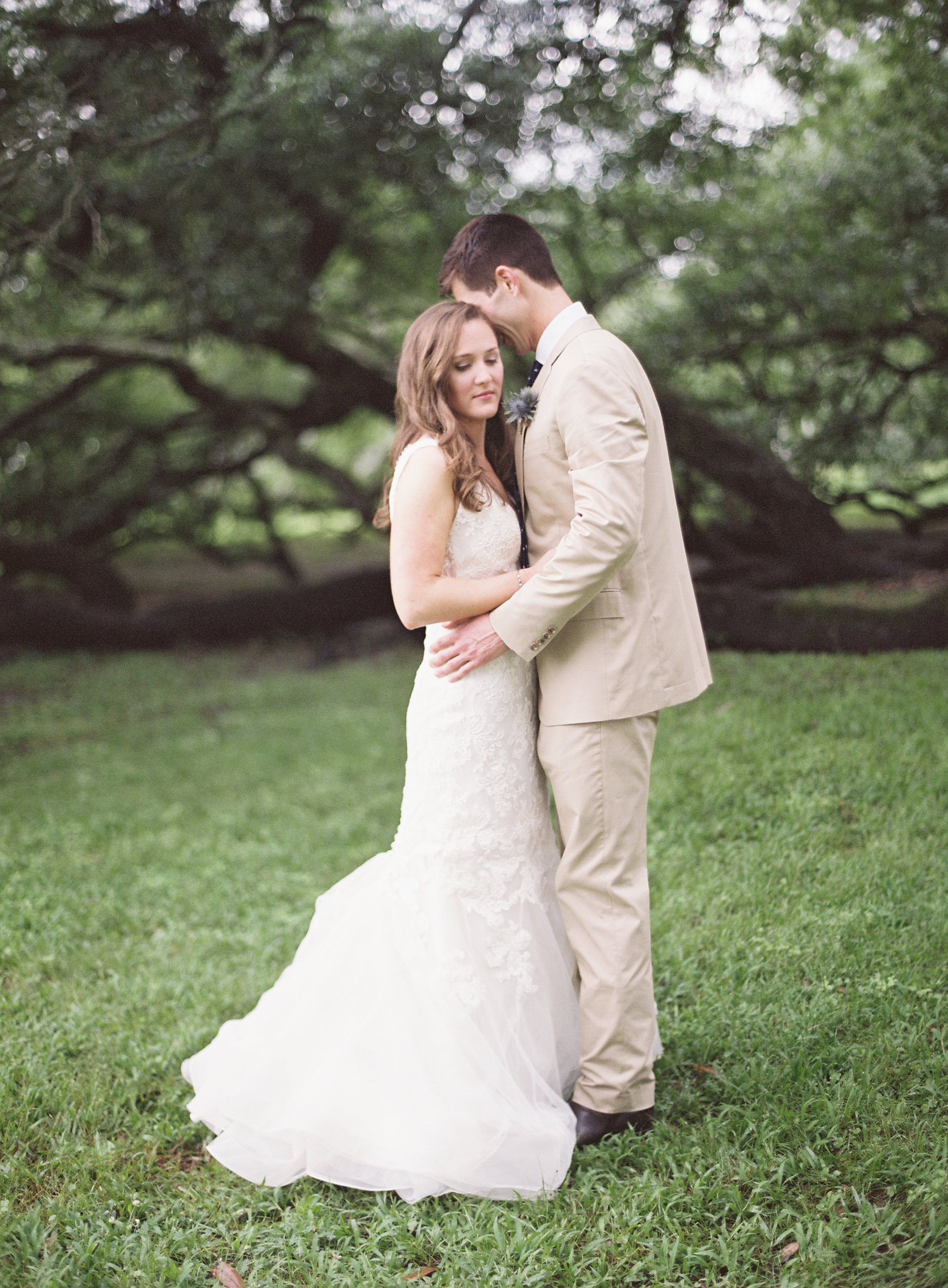 Bride and groom pose in front of oak tree