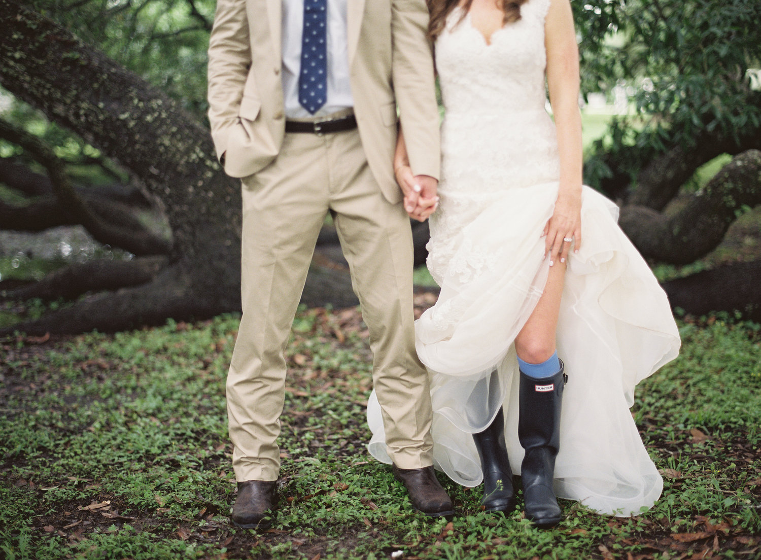 Bride and groom kiss in front of a big oak tree while the bride shows her rain boots under her dress
