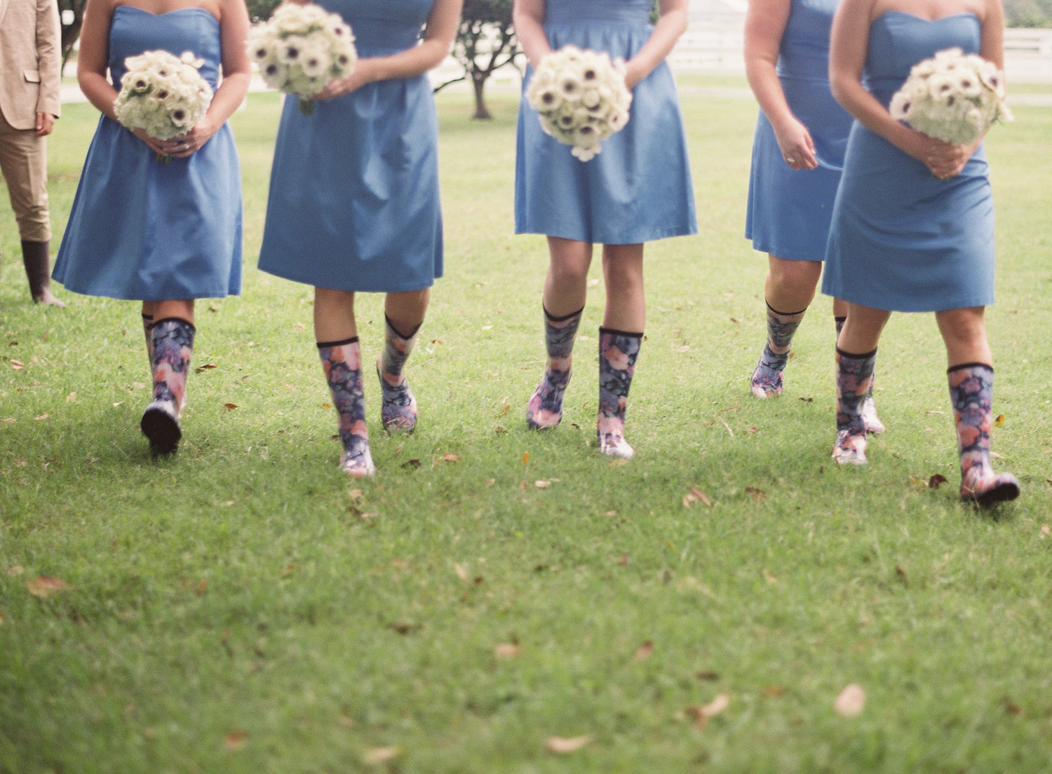 Bridesmaids walking in light blue short dresses, floral rain boots and white bouquets