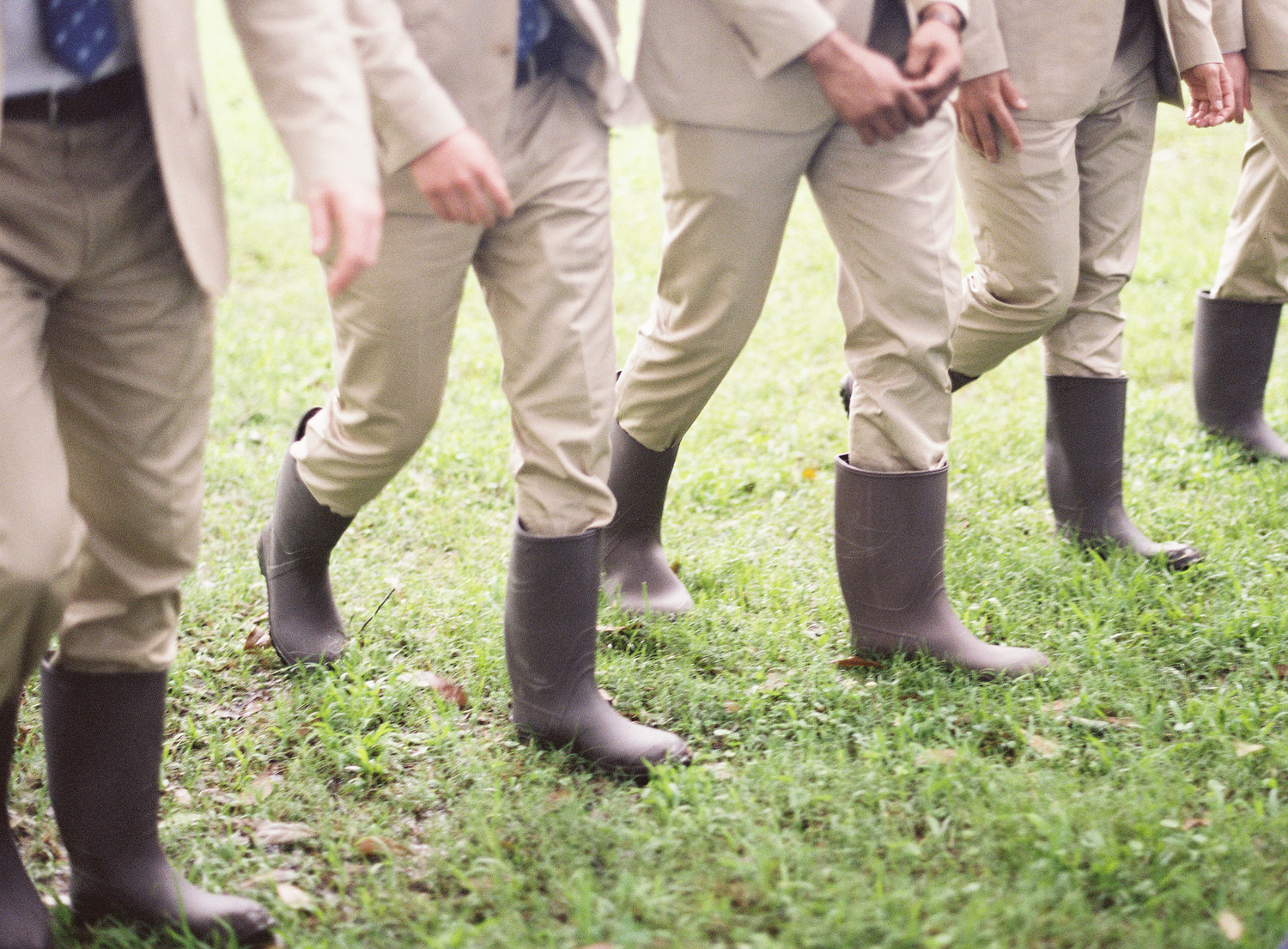 groomsmen walking in their khaki suits and dark brown rain boots