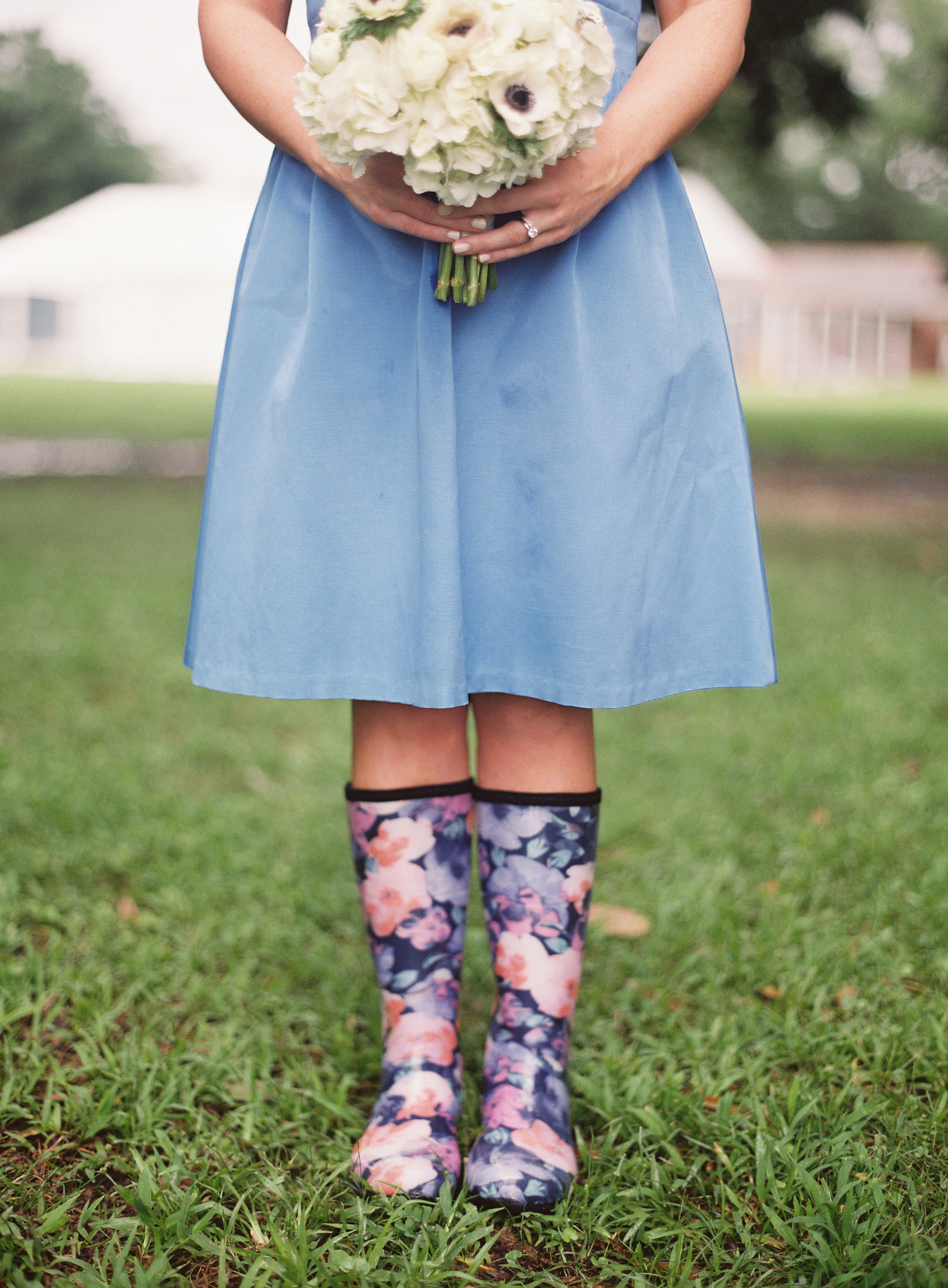 close up photo of a bridesmaid in her light blue short dress, white flowers, and pink and blue floral rain boots