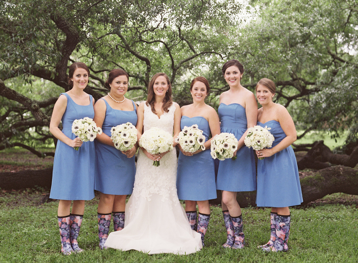 Bride and bridesmaids smiling with their rainboots on in front of oak trees and white bouquets